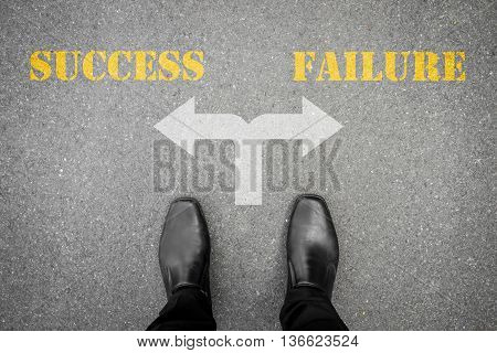 black shoes standing on the asphalt concrete floor at the crossroad - success or failure