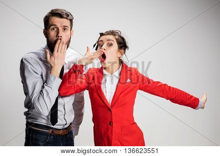 The yawning business man and woman on a gray background