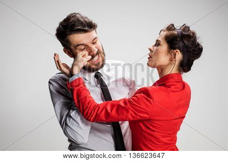 The business man and woman conflicting on a gray background. Business concept of relationship of colleagues