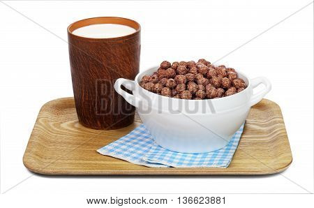 Chocolate cereal balls in a white bowl and a ceramic mug with milk on a wooden tray with paper napkins isolated on white background.
