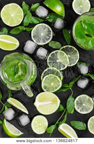 Limes, Fresh Mint And Ice On Old Grunge Black Background.