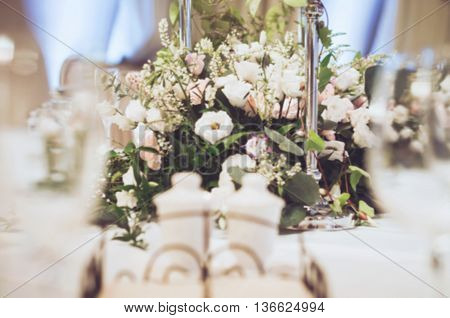 Wedding celebration wallpaper floristics background. Elegance table set in banquet restoraunt for dinning room with elegant floral composition of beige and pink roses eustoma carnations peony flowers. Place for text free copy space.