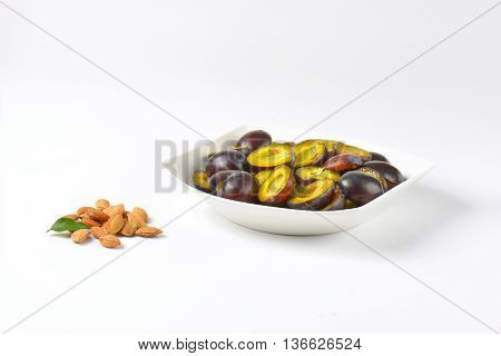 bowl of fresh plum halves and plum stones next to it