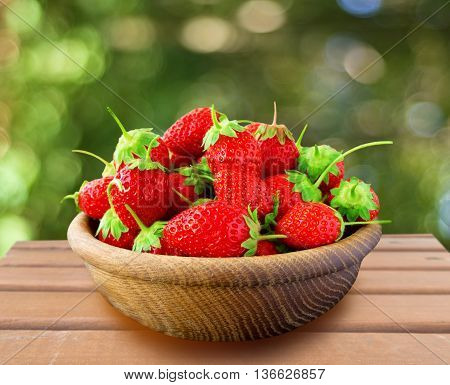 bowl with strawberries on rustic wooden background