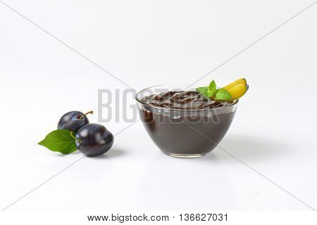 bowl of plum jam and fresh plums next to it