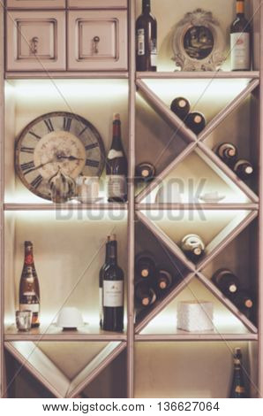 Blurred background red wine bottles stacked on wooden racks with vintage round white wall clock. Stylish fashionable composition wallpaper. Concept celebrate decoration in luxury restoraunt. Place for text free copy space.