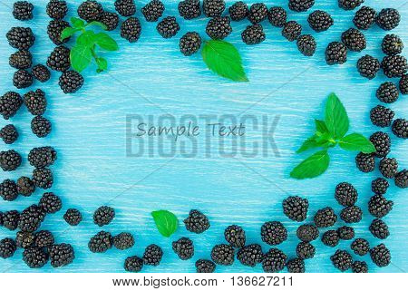 Blackberies on a blue wooden background. Free space for text.
