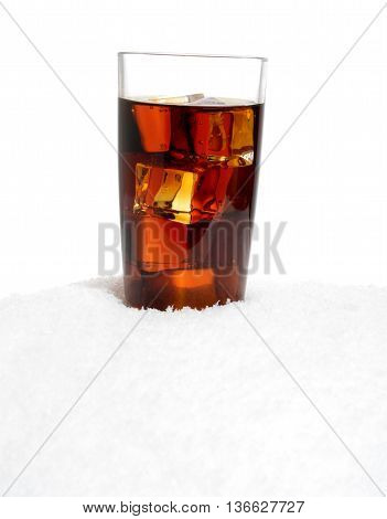 Glass of cola with ice cubes on snow on white background
