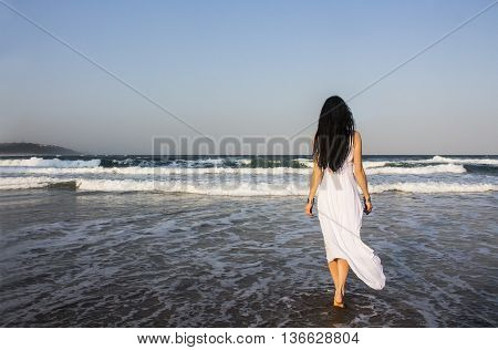 Young beautiful woman brunette with long dark hair and gold bracelets in white dress entering the Indian Ocean at sunset. Romantic style. Fashion model shot. Romance. Bohemian boho chic. Hippie style. Dreaming.