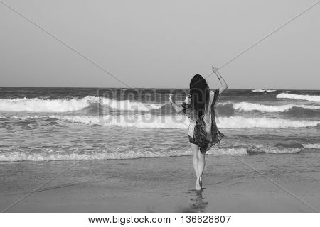 Young beautiful woman brunette with long dark hair in red white tunic dress gold bracelets entering the Indian Ocean at sunset. Romantic style. Fashion model shot. Romance. Bohemian boho chic. Hippie style. Dreaming. Black and white image.
