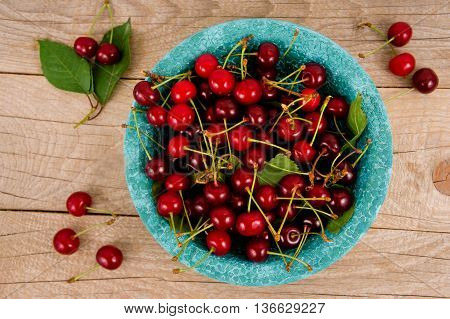 Background of ripe cherries. Cherry on blue bowl. Fresh cherries scattered on a wooden table.