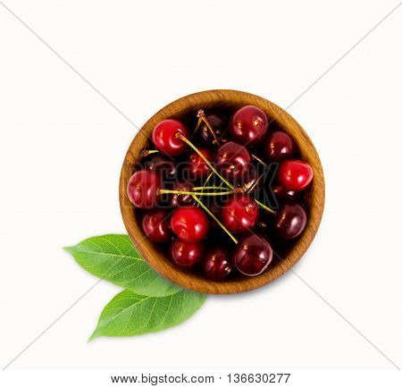 Cherries in a wooden bowl with with leaves. Top view. Ripe and tasty cherries isolated on white background. Cherries in a bowl.