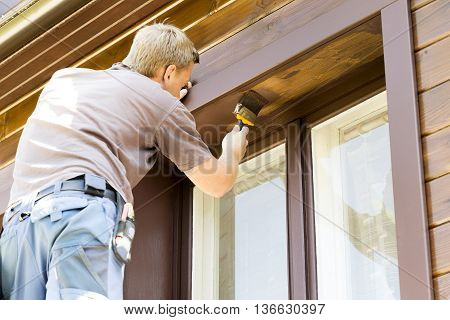 man with paintbrush painting wooden house exterior