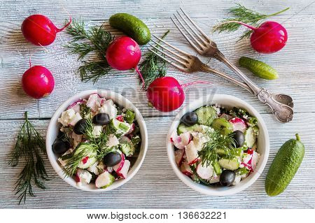 Healthy diet food: vegan vegetable salad with fresh cucumbers radish green onion black olives dill and feta cheese. In white ceramic bowl on light wooden background.