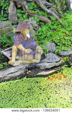 A bonsai fisherman in a small lake