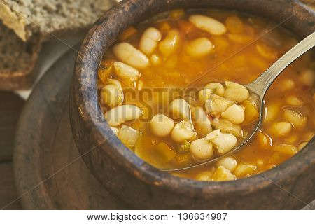 Closeup of cooked beans in clay bowl with spoon and whole wheat bread in background