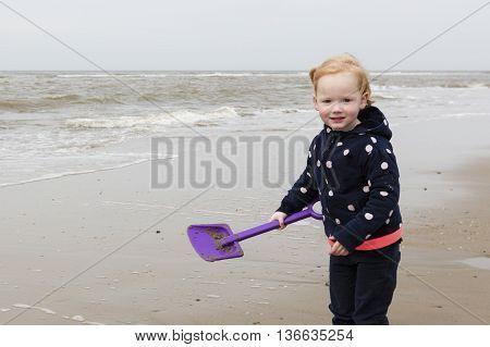 Smiling Young Girl Playing At North Sea Coast