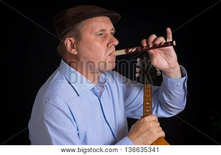 Mature musician playing Ukrainian woodwind instrument sopilka with the right hand and taking mandolin in left one
