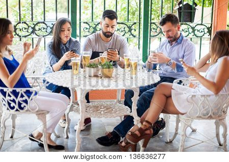 Group of young Latin friends ignoring each other and looking at their smartphones during a reunion in a backyard