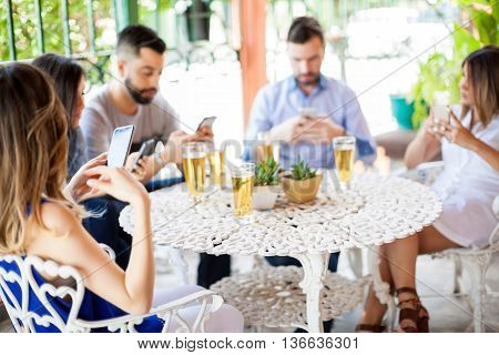 Five young Hispanic friends updating their social media status and texting during a reunion outdoors