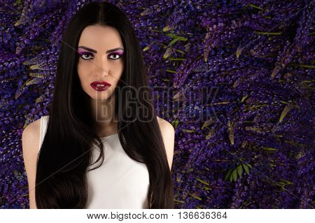 portrait beautiful woman with flowers Lupine in studio