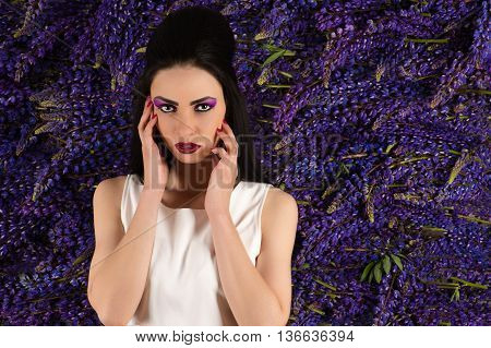 attractive woman on the background wall of flowers Lupine