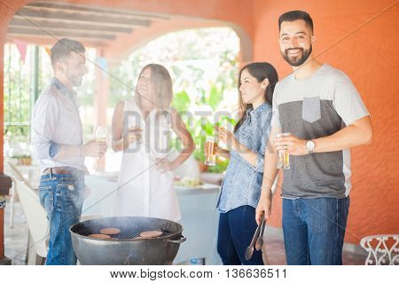 Handsome young Latin man cooking some hamburgers with his friends and drinking beer at a reunion and smiling