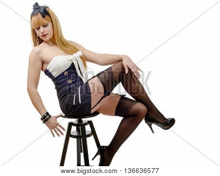 a pretty sexy woman with stockings sitting on a stool on white