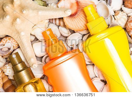Brown, orange and yellow containers of cosmetic sunscreen products with variety of shells and starfish. Skin care cosmetics containing sun protection factor for safe tan