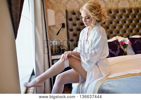 Beauty Bride In Dressing Gown Is Wearing Bridal Stockings Indoors. Beautiful Model Girl In Colorful