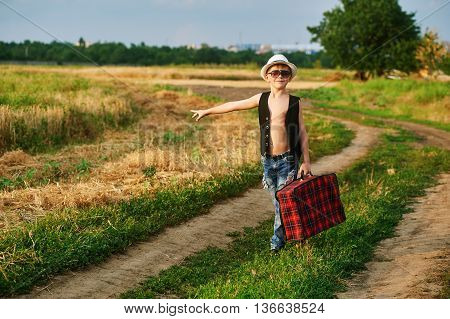 stylish boy with vintage suitcase on rural road