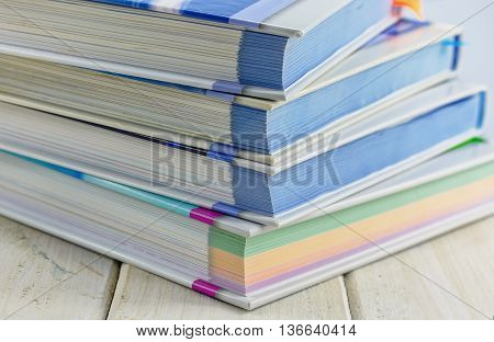 stack of books with colored pages on a wooden table.