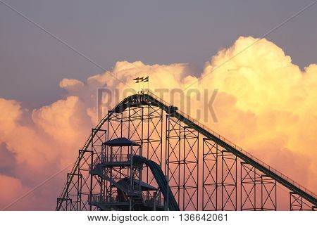 SHAKOPEE MINNESOTA USA - JUNE 22 2016: The Wild Thing roller coaster and waterpark slides at Valley Fair theme park silhouetted against dramatic cumulonimbus clouds on a warm summer evening. Valley Fair opened in 1976 and features over 75 rides.