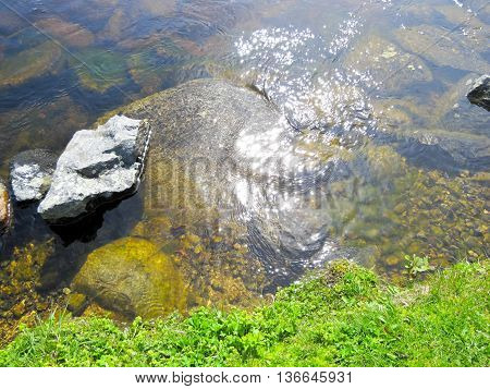 Bank of the river with stones on blue sky background