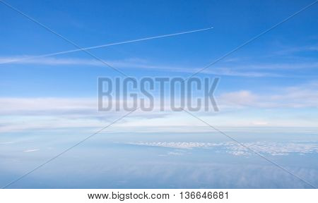 Small plane in the blue boundless sky above white clouds