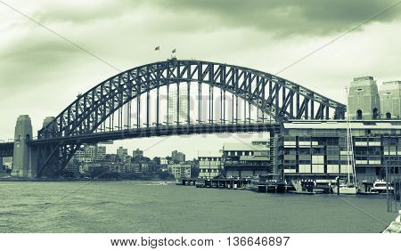 Old style image of Sydney Harbor Bridge Australia with darkening rain clouds gathering above split tone image green hue