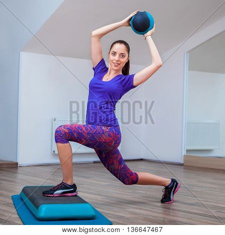 Fitness girl, wearing in sneakers, posing on step board with ball, the sport equipment background, gym