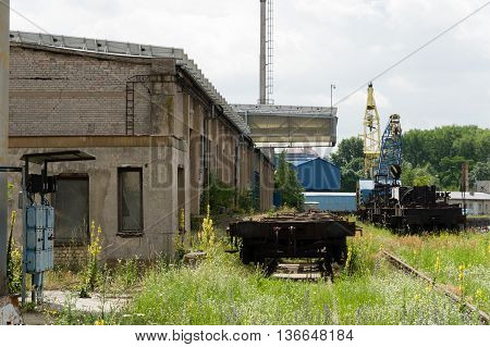Abandoned looking industrial shipyard with large crane and railtracks