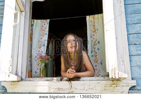 Laughing joyful little girl looking out from the window wide open