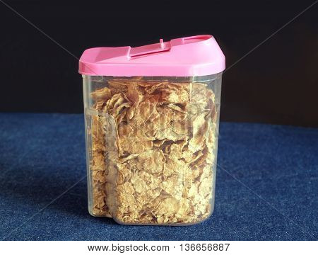 Brown corn flakes in transparent plastic container with pink cap on black background on kitchen table covered jeans tablecloth close-up view