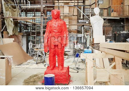 RUSSIA, MOSCOW - MAY 28, 2015: Clay sculpture covered by red silicon rubber in the workshop of sculptor Salavat Shcherbakov. It is one of the stages of manufacture of a bronze sculpture.