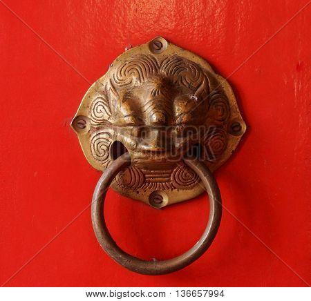 A Chinese door knob on red wooden door