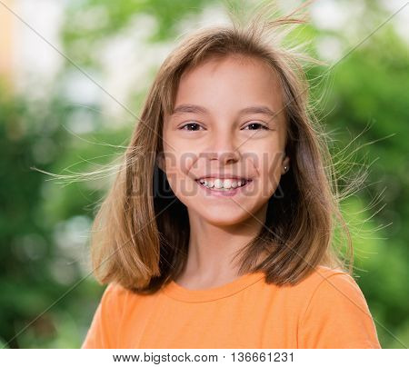 Outdoors portrait of beautiful young smiling girl
