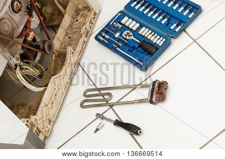 Mechanical industrial domestic electrical engineering concept. Washing machine during repair. Broken laundromat with heater removed next to tool set.