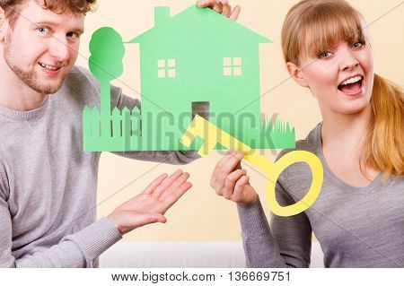 Property ownership finances family future concept. Cheerful couple holding cutouts. Young man and woman presenting small house with key.