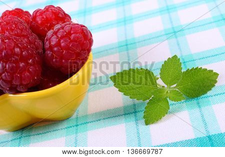 Fresh raspberries in yellow bowl and leaf of lemon balm on checkered tablecloth concept of healthy food and dessert