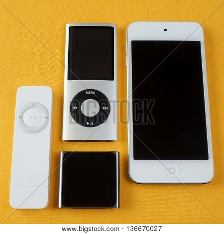 BERRY AUSTRALIA - June 20 2016 : A group of Apple iPods - iPod Nano 6th generation iPod Shuffle 1st generation iPod Touch 5th generation and iPod Nano 4th generation - on a plain yellow background.