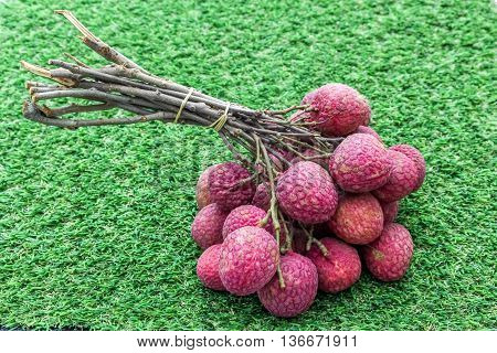 Isolated bunch of lychee on the grass background