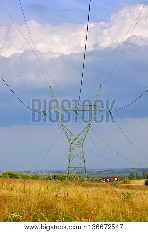 Electricity transmission pylon and overhead lines crossing Polish countryside.