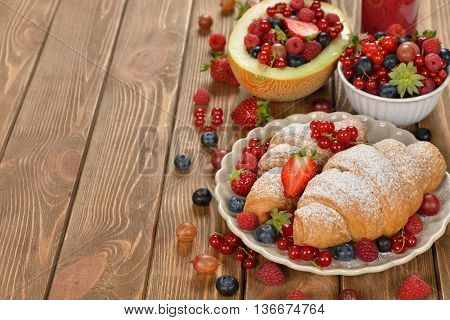 Croissants with berries on brown background close up